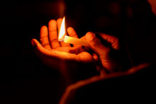 Hands holding a lit match and shining a light