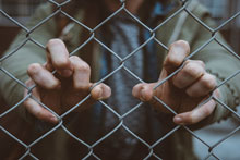 Image of hands holding prison fence